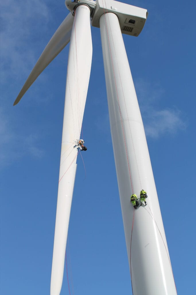 Workers hanging from a wind turbine.
